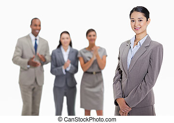 Businesswoman with co-workers applauding in the background