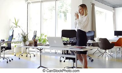 Businesswoman with coffee in her office working on laptop.