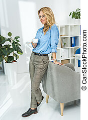 businesswoman with coffee in modern office