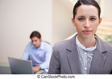 Businesswoman with colleague on his laptop behind her