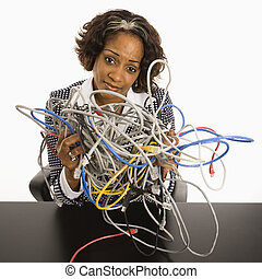 Businesswoman with computer cords. - Businesswoman holding...