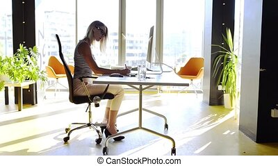 Businesswoman with computer in her office at the desk, working.