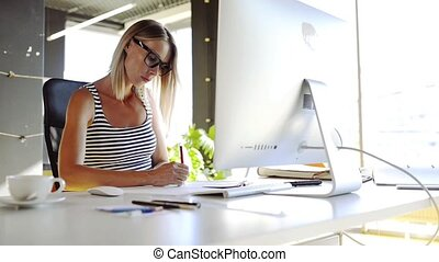 Businesswoman with computer in her office, working.