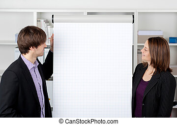 Businesswoman With Coworker Looking At Flip Chart