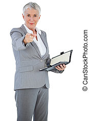 Businesswoman with diary pointing her finger at camera