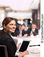 Businesswoman with digital tablet. Rear view of cheerful young woman in formalwear working on digital tablet and looking over shoulder while sitting at the restaurant