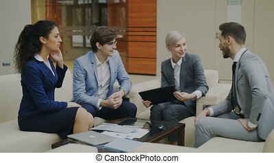 Businesswoman with digital tablet talking with male and femalebusiness colleagues sitting on couch in modern office