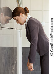 Businesswoman in fatigue leaned her head on wall.