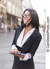 Businesswoman with glasses and tablet on street
