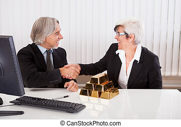 Gleeful businesswoman grabbing hold of a stack of gold bullion bars as she reaps the rewards for astute business practices and investments