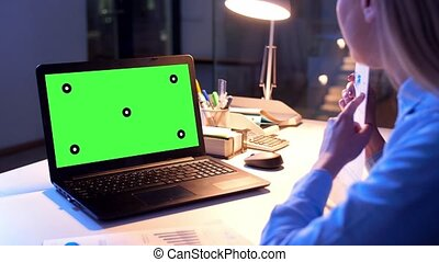 businesswoman with green screen on laptop at night -...