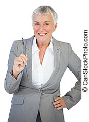 Businesswoman with hand on hip holding pen