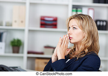 Businesswoman With Hands Clasped Looking Away In Office
