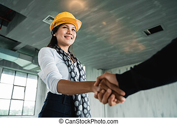 businesswoman with hardhat shaking hand