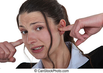 Businesswoman with her fingers in her ears