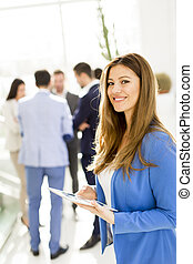 Businesswoman with her tablet standing in the office