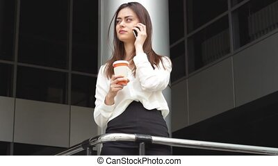 Businesswoman with hot drink talking using smartphone -...