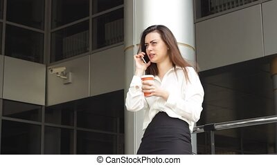Businesswoman with hot drink using smartphone - Beautiful...