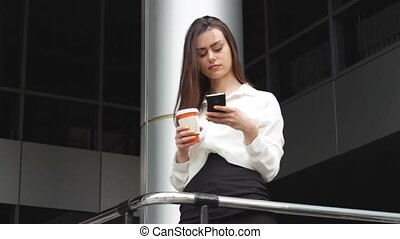 Businesswoman with hot drink using smartphone with office...
