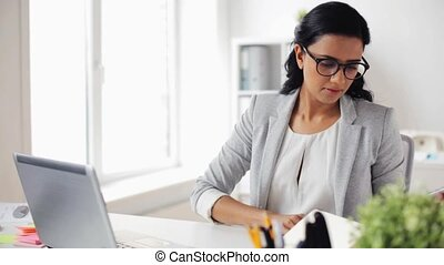 businesswoman with laptop and calculator at office -...