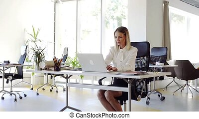 Businesswoman with laptop in her office at the desk,...