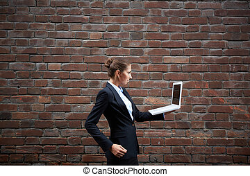 Businesswoman with laptop - Image of serious businesswoman...