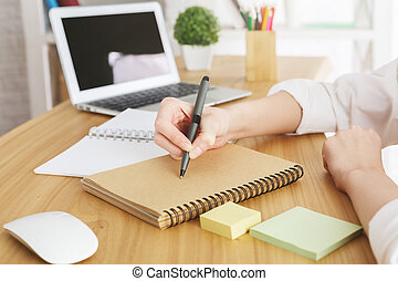 Businesswoman with laptop writing in notepad - Close up of...