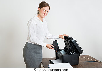 Businesswoman With Laser Cartridge And Printer At Desk - ...