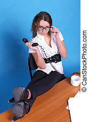 Businesswoman with legs on the desk