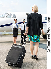 Businesswoman With Luggage Walking Towards Private Plane -...