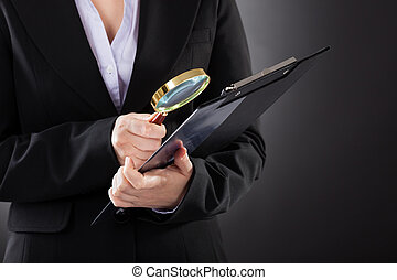 Businesswoman With  Magnifying Glass And Clipboard