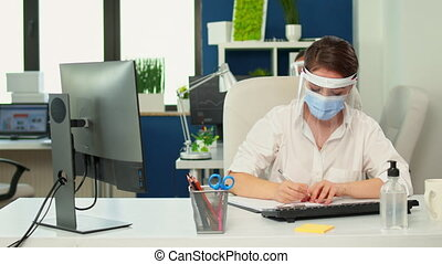 Businesswoman with visor and protection mask analysing financial annual statisctics taking notes on clipboard in new normal business office. Employees working in company respecting social distance.