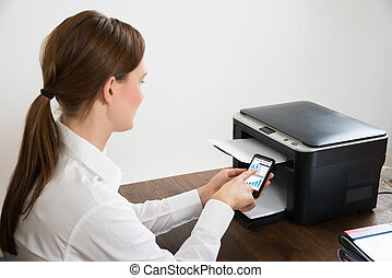 Businesswoman With Mobile Phone Connected To Printer