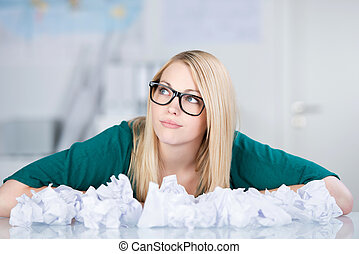 Businesswoman With Paper Balls On Desk Looking Away