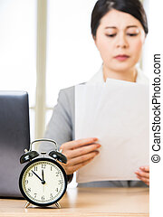 Businesswoman with papers over table with alarm clock laptop