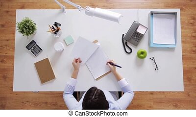 businesswoman with papers working at office desk