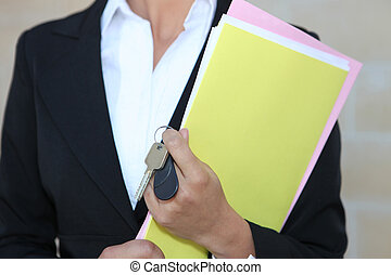 Businesswoman with paperwork and keys