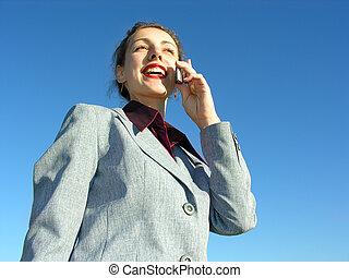businesswoman with phone on blue sky from down view