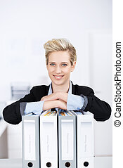 Businesswoman With Ring Binders At Desk