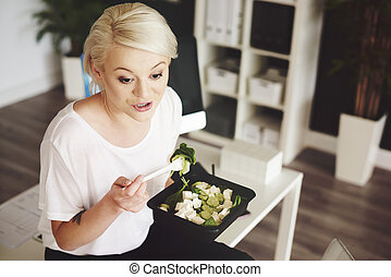 Businesswoman with salad talking while lunch hour