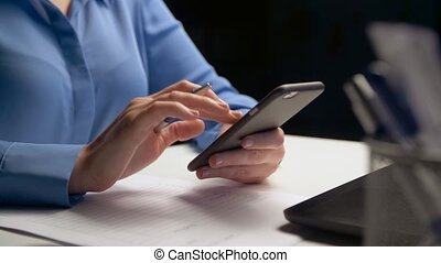 businesswoman with smartphone at night office - business,...