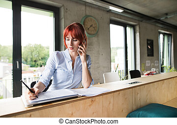 Businesswoman with smartphone in her office.