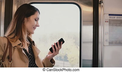 Businesswoman with smartphone in subway car. Pretty young female commuter using messenger app online. Wireless 5G. 4K