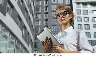 Businesswoman with Tablet in front of Corporation