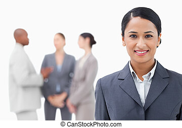 Businesswoman with talking associates behind her