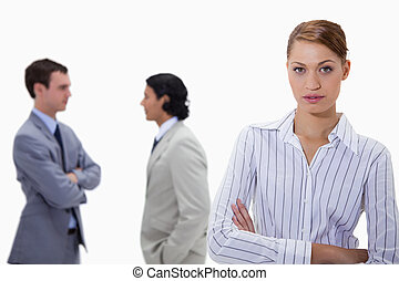 Businesswoman with talking colleagues behind her