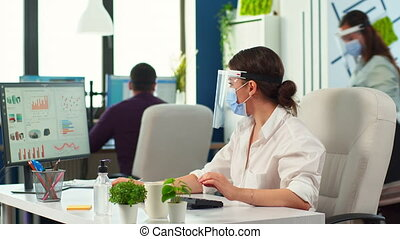 Businesswoman with visor and protection mask working in new normal financial business office. Coworkers advising in background, company team respecting social distance during global pandemic.