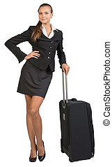 Businesswoman with wheeled travel bag, hand on hip