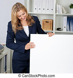 Businesswoman With White Billboard In Office
