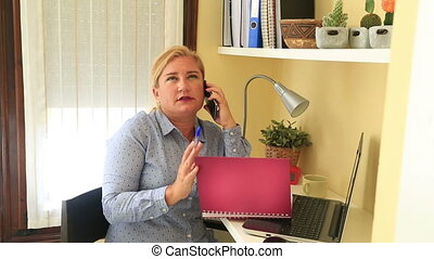 Businesswoman working at home - Businesswoman talking on the...